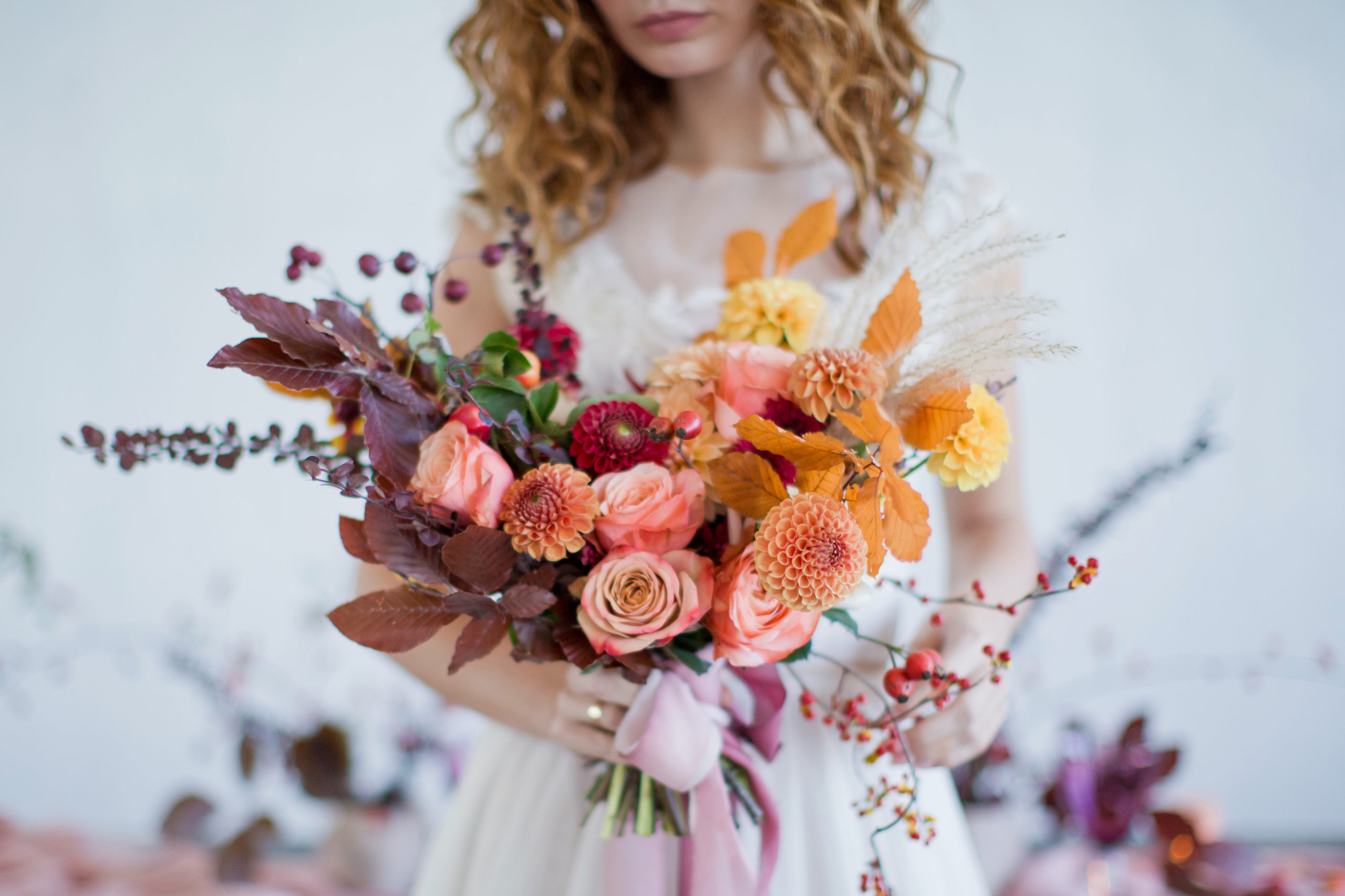 Bride holds beautiful autumn bouquet with orange and red flowers and berries. Autumn bouquet with ribbons in bride's hands